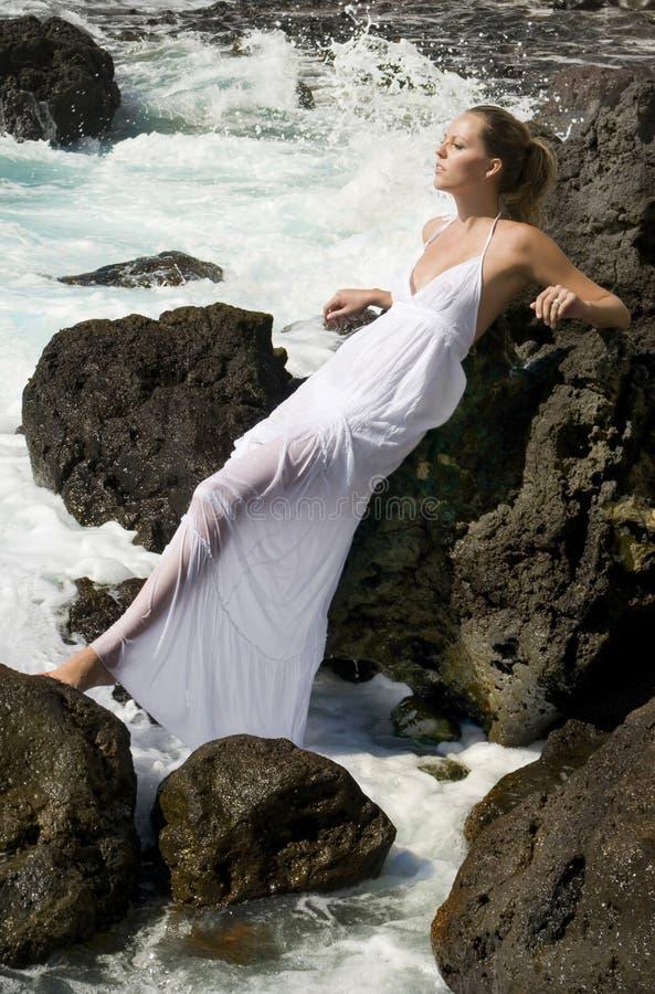 Sorglose Frau im weißen Kleid im Ozean stockfotos