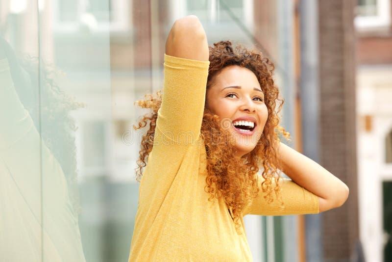 Sorglose junge Frau, die mit den Händen hinter Hauptaußenseite lacht stockbilder