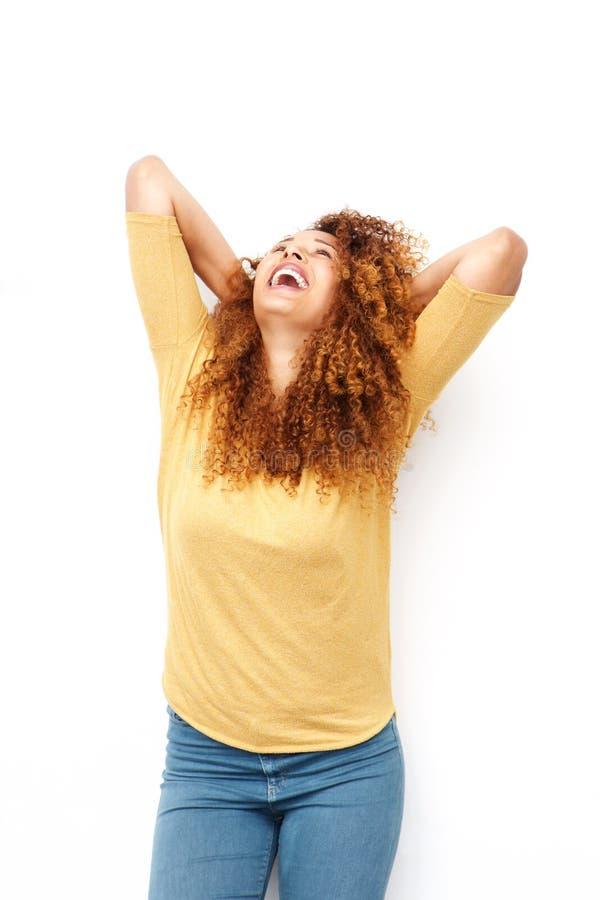 Sorglose junge Frau, die mit den Händen hinter Kopf lacht lizenzfreie stockfotos
