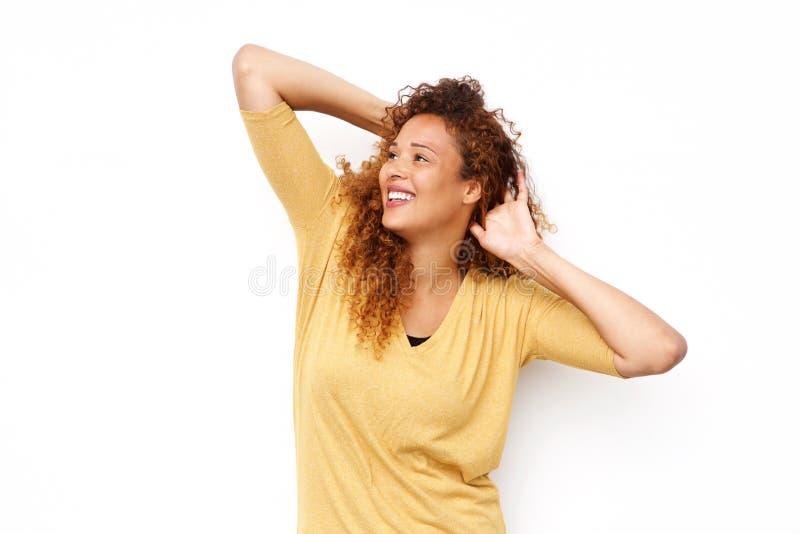 Sorglose junge Frau, die mit den Händen im Haar gegen lokalisiertes weißes backgroun lächelt stockfotos