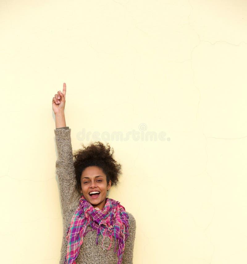 Sorglose junge Frau, die oben Finger zeigt stockfoto