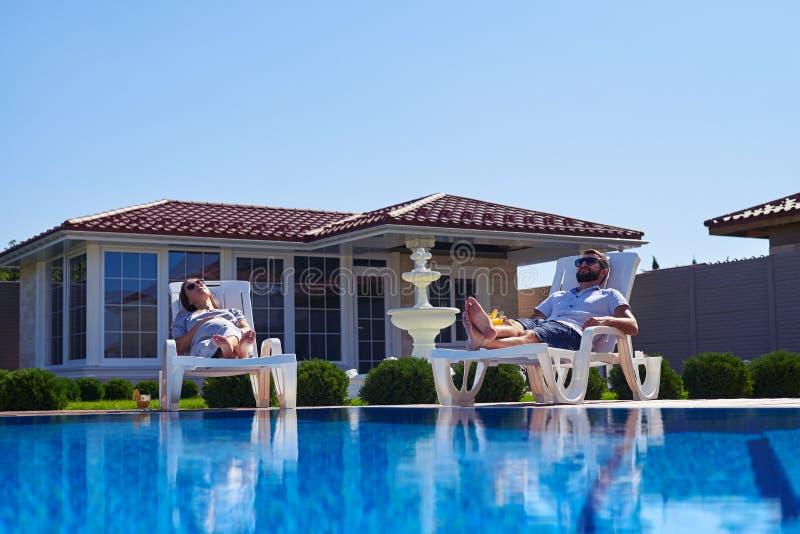 Sorglose Paare, die Sonnenbräune unter der Sonne nahe Pool erhalten lizenzfreies stockbild