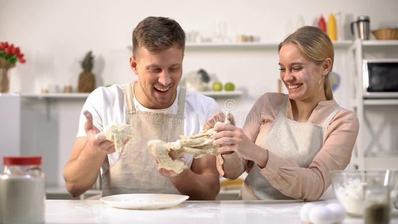 Sorglose Paare, die unbeholfen Teig, Spaß in der Küche, unfähige Chefs habend kneten stockfotografie