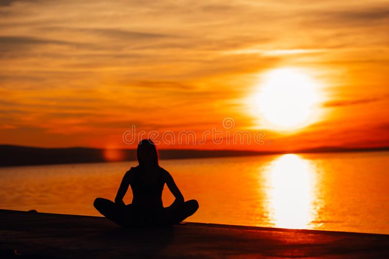 Sorglose ruhige Frau, die in der Natur meditiert Finden des inneren Friedens Bemannen Sie das Handeln der Hälfte, die in einer si lizenzfreies stockfoto