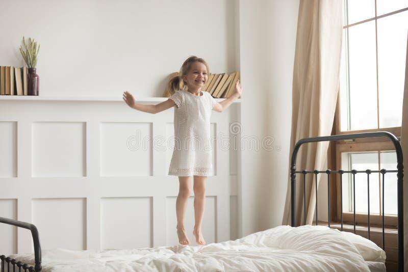 Sorgloses aktives tragendes weißes Kleid des kleinen Mädchens, das auf Bett springt stockbilder