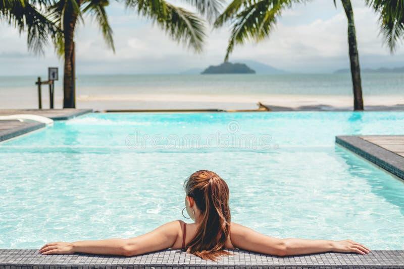 Sorgloses Frauenentspannung im Swimmingpool-Sommerferienkonzept stockbilder