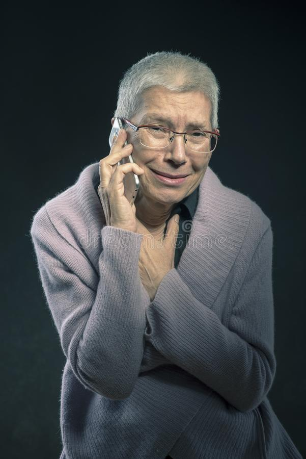 Sorgsen farmor som mottar ruskig nyheterna på telefonen arkivfoton