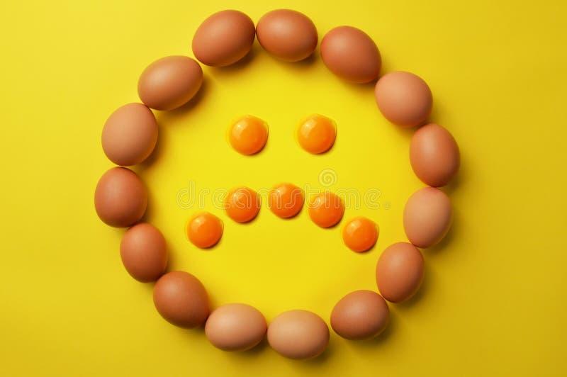 Sorgsenhetemoticonframsida med rå ägg och äggulor arkivbilder