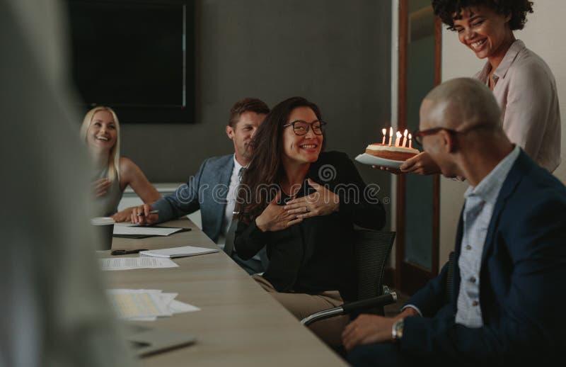 Sorprenda la celebración del cumpleaños de un socio durante la reunión foto de archivo libre de regalías