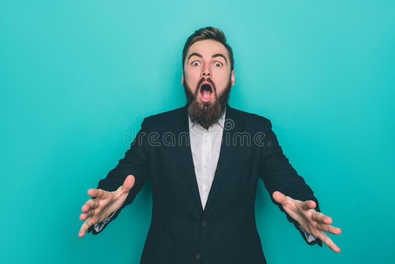 Sorprenden al hombre de Berded absolutamente Él está mirando al awith de la cámara que su boca se abrió También él está mostrando imágenes de archivo libres de regalías