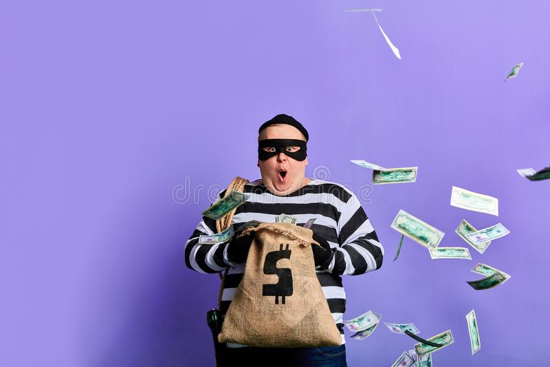 Sorprenden al ladrón regordete en mucho dinero en el saco foto de archivo libre de regalías