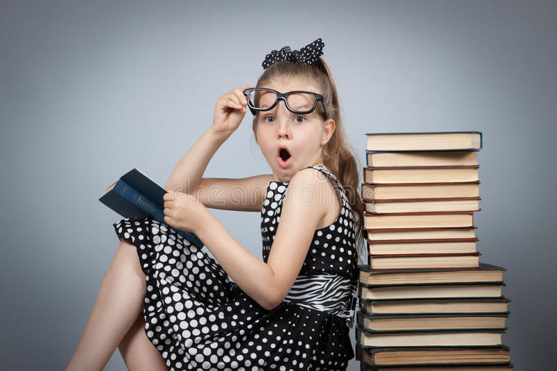 Sorprenden a la muchacha que lee un libro y muy imagen de archivo libre de regalías