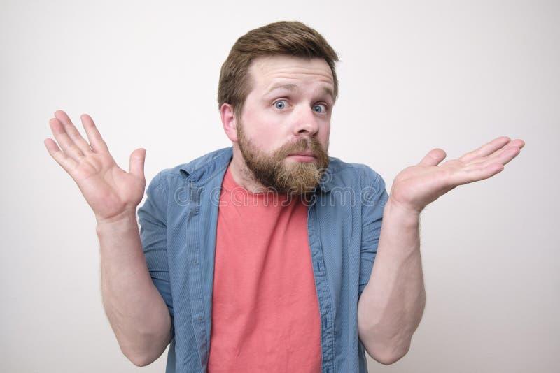 Sorprenden y se desconciertan al hombre joven, barbudo, y aumenta sus manos en la confusi?n Aislado en el fondo blanco fotos de archivo libres de regalías