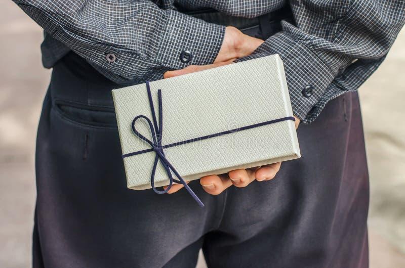 Sorprendente lei retrovisione dell'uomo in camicia che tiene un contenitore di regalo dietro il suo indietro mentre stando contro fotografia stock