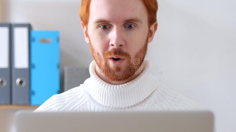 Sorprendido por progreso positivo inesperado, el hombre con los pelos rojos y la barba fotos de archivo libres de regalías