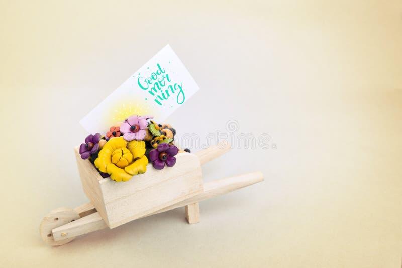 Sorpresa de la mañana, carretilla con las flores y una tarjeta Una inscripción coloreada es una buena mañana imagen de archivo libre de regalías
