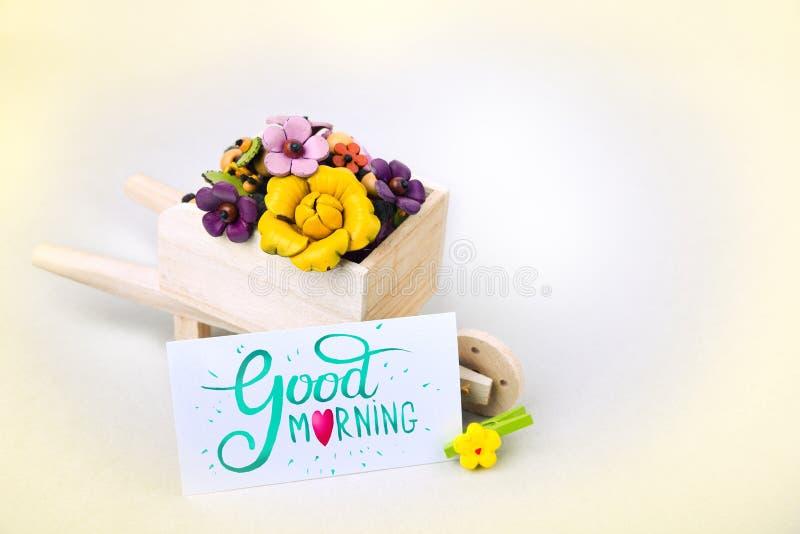 Sorpresa de la mañana, carretilla con las flores y una tarjeta Una inscripción coloreada es una buena mañana fotos de archivo libres de regalías
