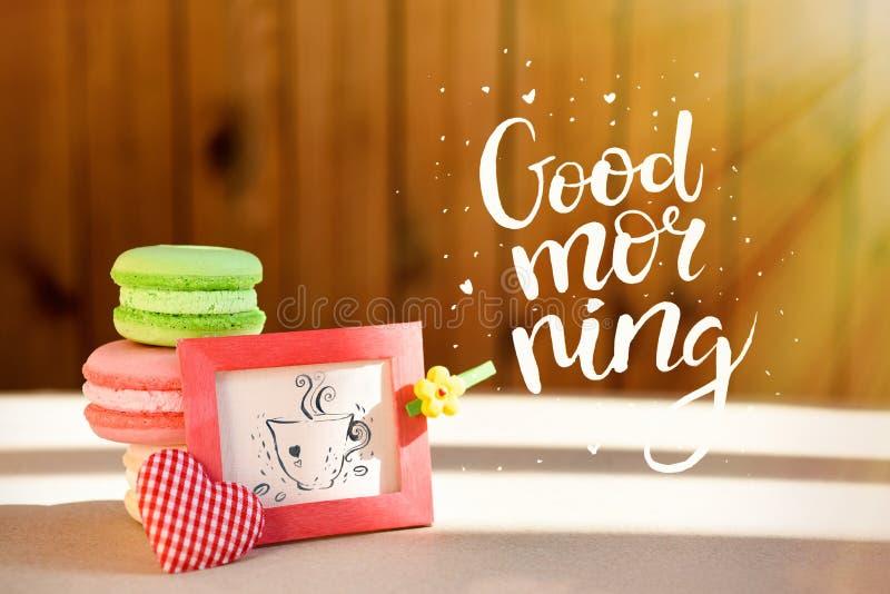 Sorpresa de la mañana, makarons coloreados de las tortas con una tarjeta La inscripción es una buena mañana Rayos de Sun foto de archivo