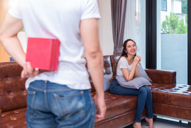 Sorpresa del muchacho su novia asiática sosteniendo la caja de regalo detrás de él en su hogar El día de tarjeta del día de San V foto de archivo libre de regalías