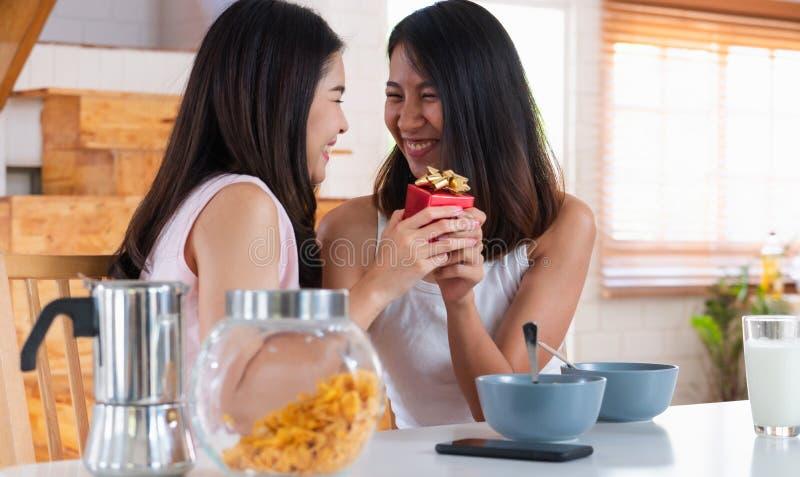 Sorpresa lesbiana asiática de los pares dando el regalo para el aniversario del amor en el tiempo de desayuno de la cocina en cas fotos de archivo