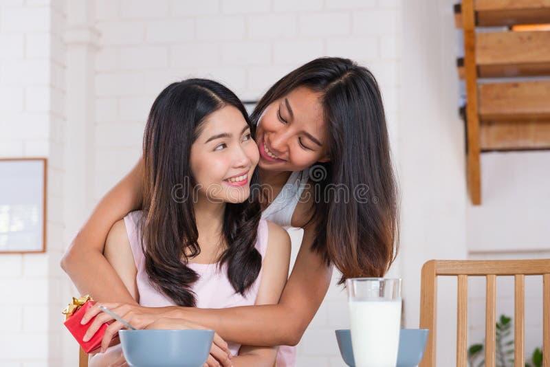 Sorpresa lesbica asiatica delle coppie dando regalo per l'anniversario di amore ad ora di colazione della cucina a casa Concetto  immagine stock libera da diritti
