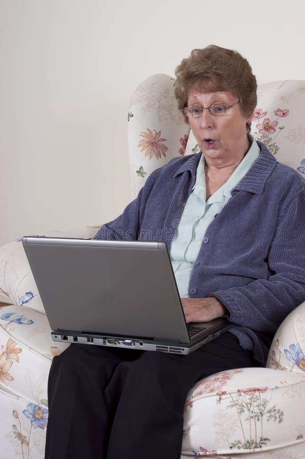 Sorpresa mayor madura del choque del ordenador portátil de la mujer fotos de archivo libres de regalías