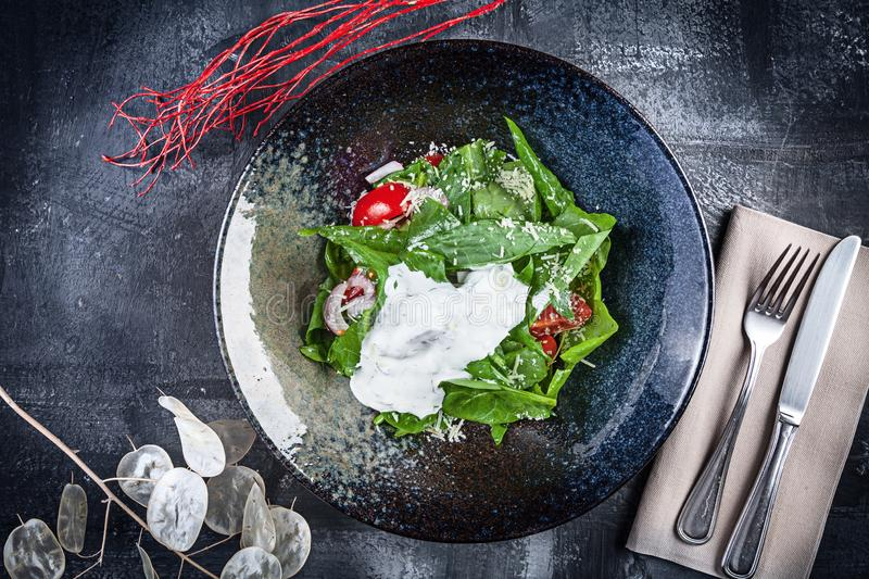 Sorrel salad with tomatoes and sour cream.Top view. Flat lay food. Fresh, green, vegan salad for lunch. Salad in black bowl on royalty free stock photos