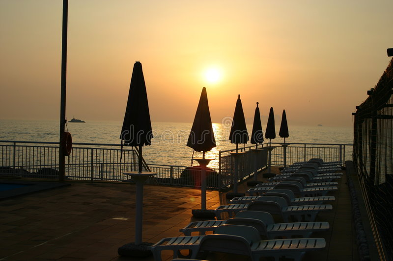 Sorrento. Deck of ship or patio with umbrellas and lounge chair, overlooking Mediterranean sea, Sorrento, Italy,sunset royalty free stock images