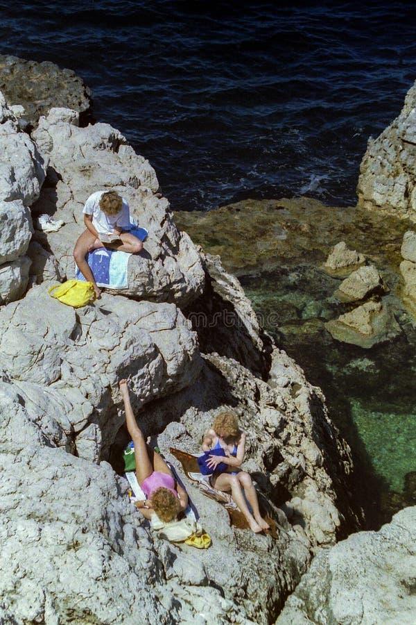 SORRENTO, ITALIË, 1984 - Drie blondetoeristen ontspant in de zon op de rotsen van de Baden van Koningin Giovanna in Sorrento stock foto's