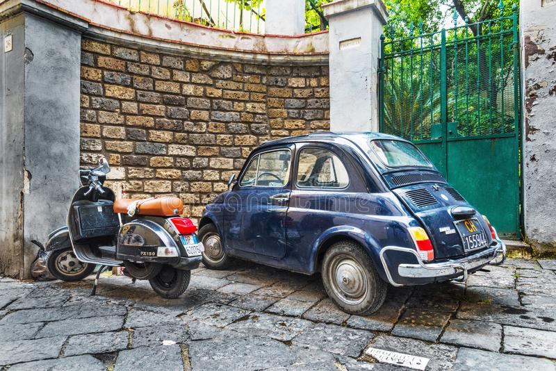 Vintage Vespa scooter and Fiat 500 parked in a picturesque narrow street stock photos