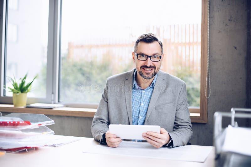 Sorridendo 40 anni dell'uomo d'affari bello che lavora al computer portatile in ufficio fotografia stock