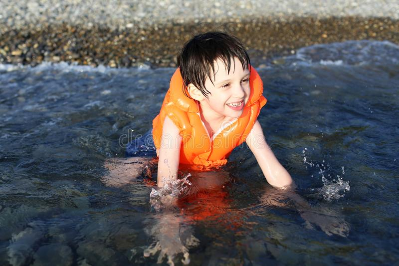 Sorridendo 5 anni di nuoto del ragazzo nel mare immagine stock libera da diritti