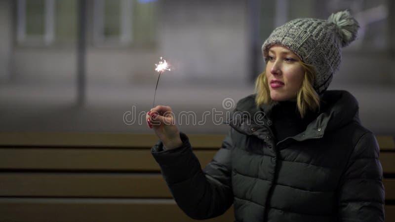 Sorridendo, bella ragazza in cappello tricottato e piumino nella via alla notte con la stella filante, celebrante nuovo anno, all fotografia stock