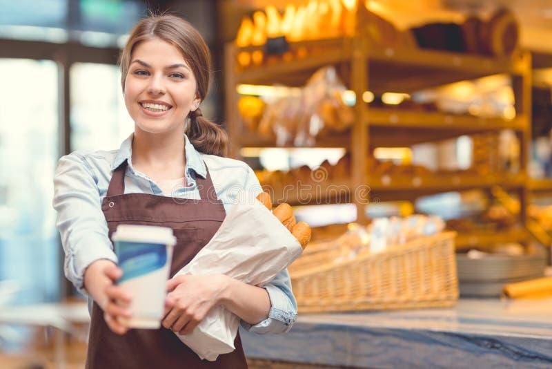 Sorridendo con il caffè in un forno fotografie stock libere da diritti