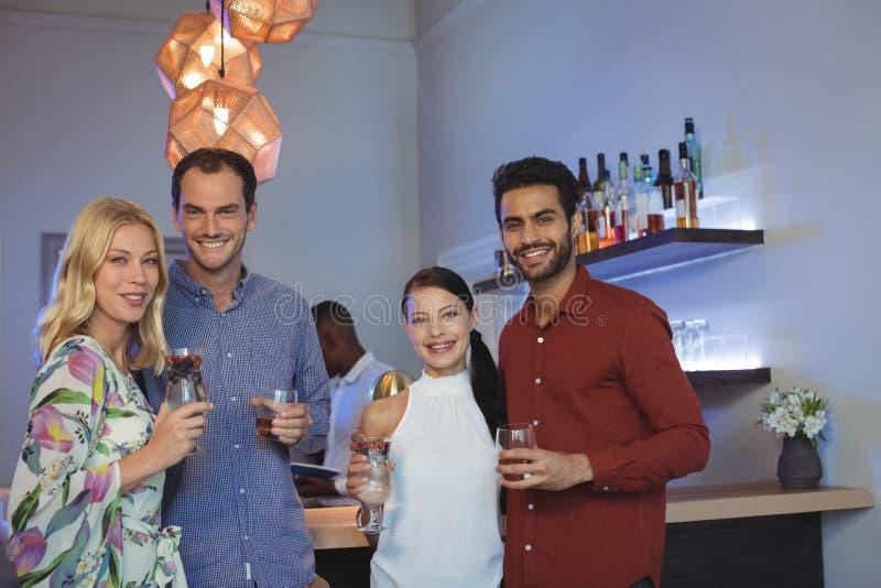 Sorridendo due coppie che hanno cocktail insieme nel ristorante della barra immagini stock libere da diritti