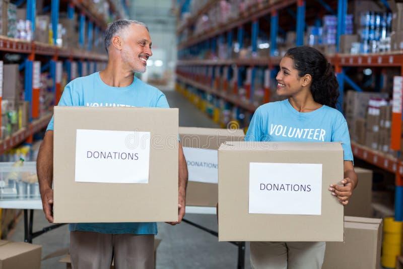Sorridendo due volontari che tengono una scatola di donazioni fotografia stock