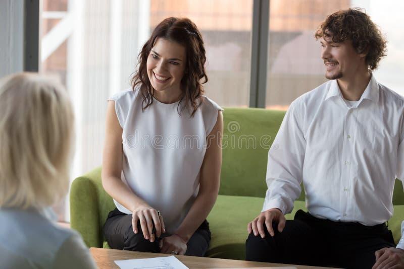 Sorridendo i suoi dirigenti che tengono un colloquio di lavoro con un candidato maturo in carica fotografia stock