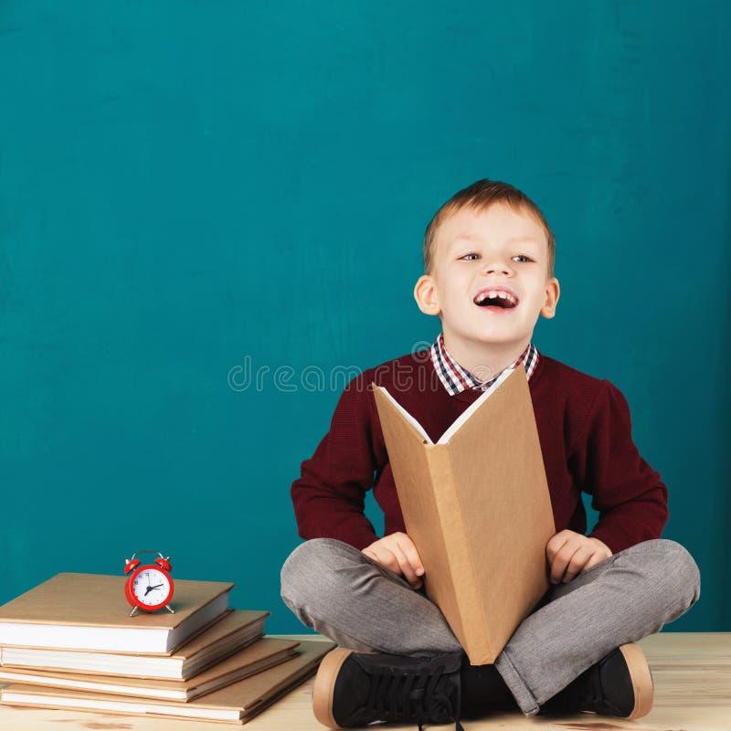 Sorridere allegro poco ragazzo di scuola che si siede su uno scrittorio contro il tur fotografie stock libere da diritti