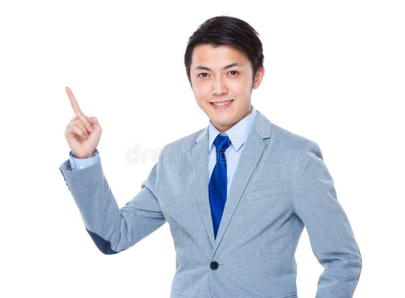 Sorridere asiatico e dito dell'uomo di affari che indicano su immagini stock