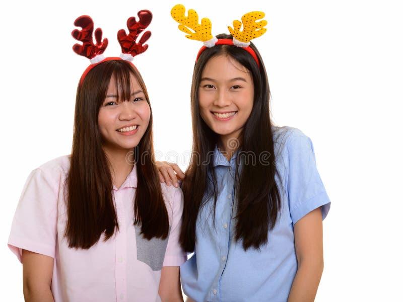 Sorridere asiatico felice di due giovane adolescenti pronto per il Natale immagine stock libera da diritti