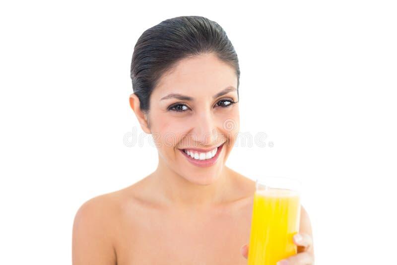Sorridere castana alla macchina fotografica che tiene vetro di succo d'arancia fotografia stock libera da diritti