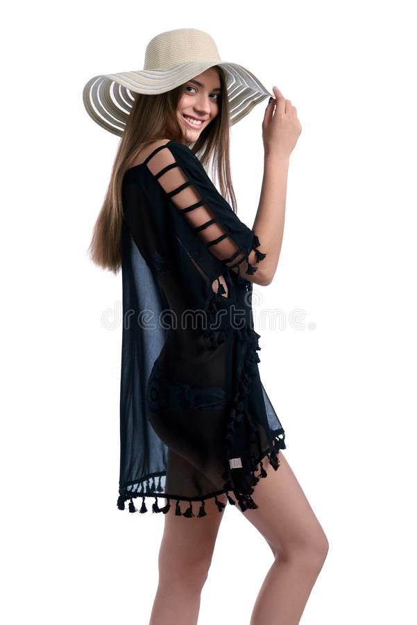 Sorridere castana attraente alla macchina fotografica mentre posando in pareo e costume da bagno scuri con il cappello bianco fotografia stock