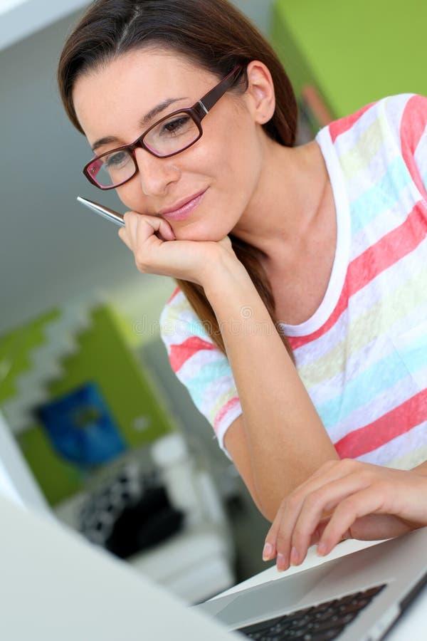 Sorridere castana con gli occhiali facendo uso del computer portatile fotografia stock libera da diritti