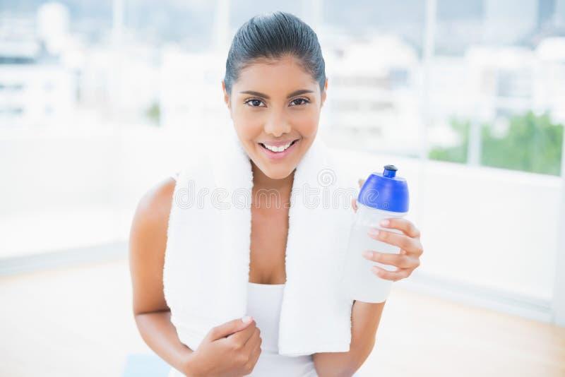 Sorridere castana tonificato con la tenuta dell'asciugamano mette in mostra la bottiglia immagini stock libere da diritti