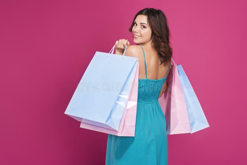 Sorridere castana in un vestito blu con le borse del regalo sta indietro fotografie stock libere da diritti