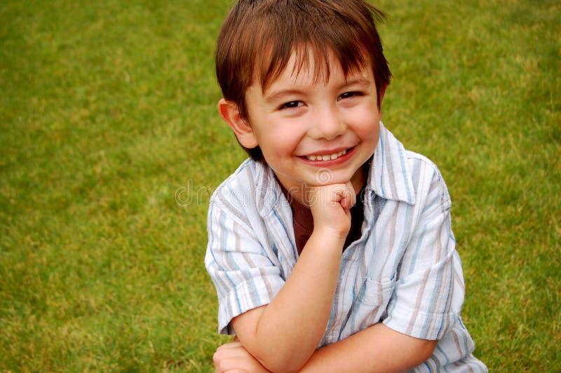 sorridere dell'erba del ragazzo immagini stock