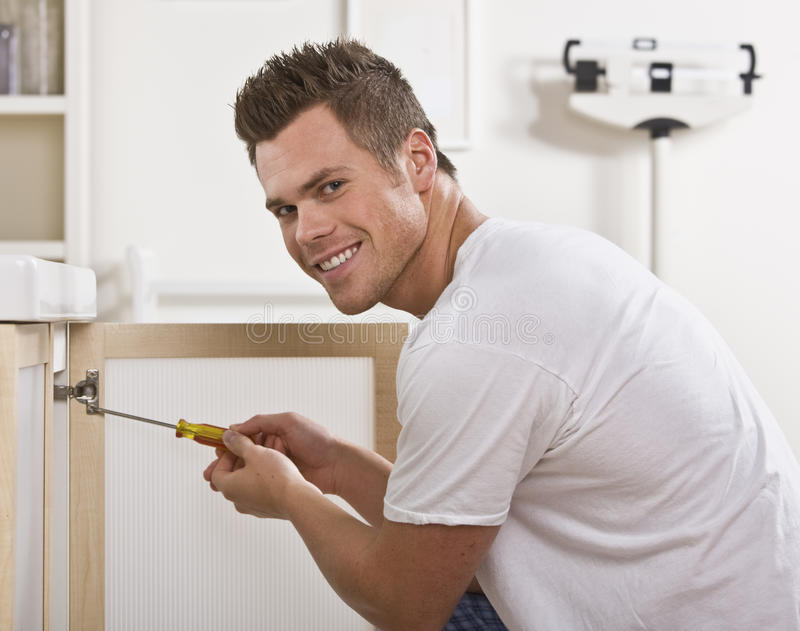sorridere dell'uomo della riparazione del portello di armadietto fotografie stock libere da diritti