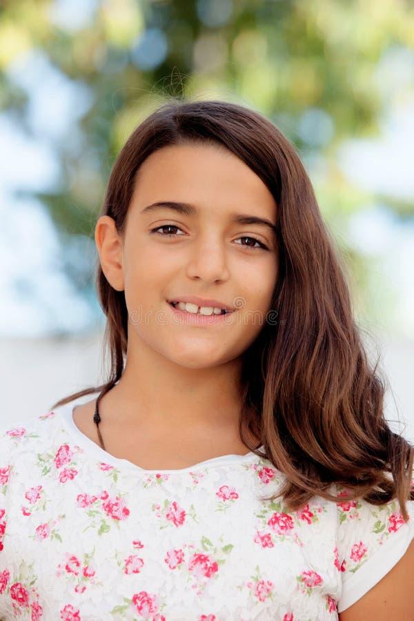 Sorridere di dieci anni della ragazza piacevole del bambino alla macchina fotografica fotografia stock