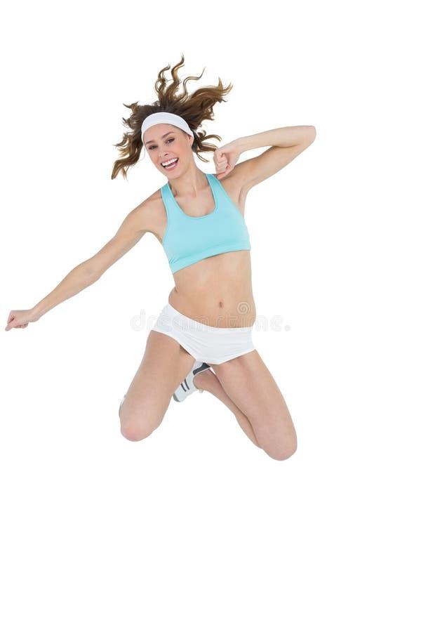 Sorridere di salto d'uso degli abiti sportivi della giovane donna contenta alla macchina fotografica immagini stock