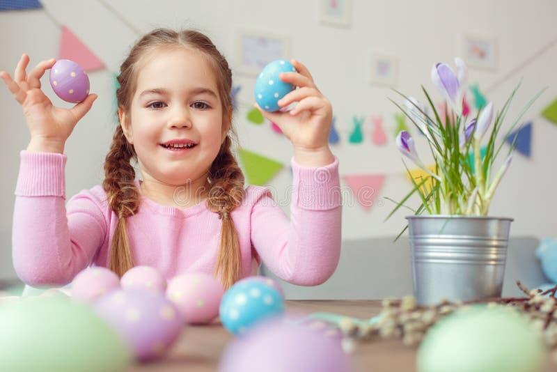 Sorridere di seduta delle uova della tenuta due di piccolo della ragazza di pasqua concetto sveglio di celebrazione a casa fotografia stock